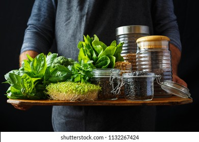 Man holds set healthy food, protein source for vegetarians: spinach, basil, parsley, broccoli, quinoa, black beans, green lentils, chickpeas and buckwheat