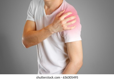 A man holds the shoulder. The pain in my arm. Sore point highlighted in red. Closeup. Isolated.