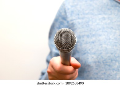 A man holds a silver, gray microphone in his hand and conducts business interviews, journalistic reporting, public speaking, press conference, sings karaoke
