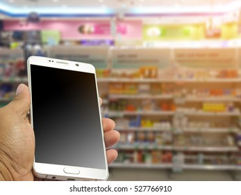 A man holds a smart phone in the drugstore.