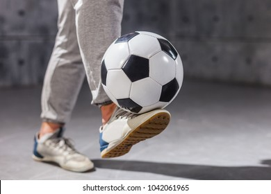 Man holds a soccer ball on his leg. Close-up