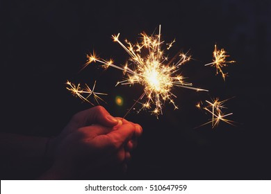 Man holds sparkler in the night.
