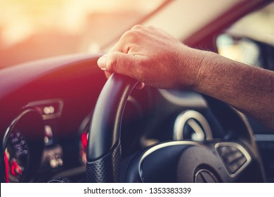 A man holds the steering wheel of a car