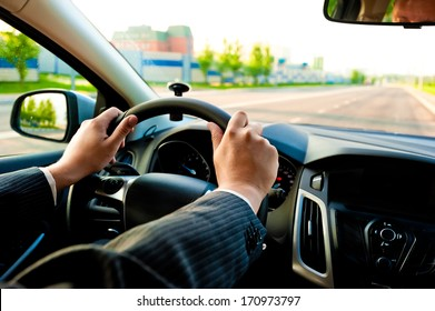 man holds the steering wheel firmly with both hands