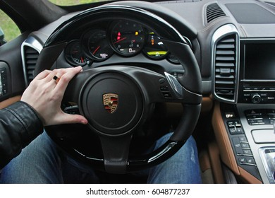 A man holds the steering wheel of a luxury car. Gold ring on his hand. Porsche Cayenne. Editorial photo. Ukraine, Kiev. March 20, 2015.