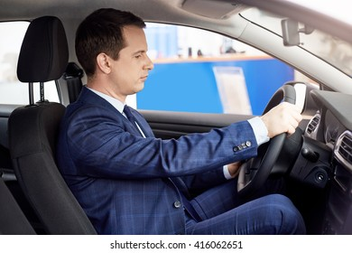 A man holds the steering wheel, shot inside the car