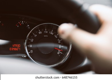 Man holds steering wheel and speedometer show hi speed