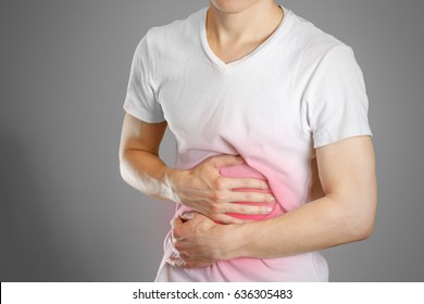 A man holds the stomach. The pain in his chest. Heartburn. Stomach hurts. Sore point highlighted in red. Closeup. Isolated.