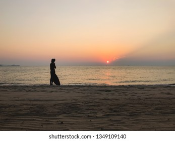 A man holds surfboard and finding sea wave for surfing at sunset on the sea