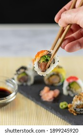 Man holds sushi chopsticks over the rest of the Sushi plate. Selective focus