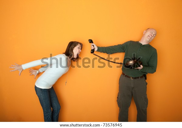 Man holds telephone while angry woman shouts into it