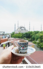 Man holds a traditional cup of coffee in his hand with a Blue mosque Sultanahmet Camii background.Travel to Istanbul, Turkey. Soft focus and beautiful bokeh.