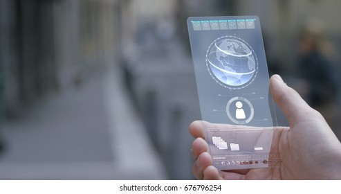 A man holds a transparent mobile phone of the future, a touchpad, the globe, contacts, a person's hand. Concept: new technology, telephone communication, Internet, a network, new ideas, future people.