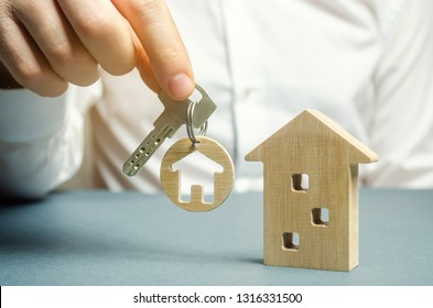 A man holds a trinket key with a house and a wooden home. Real estate concept. Realtor services. Sale of property. Buy housing. Apartments for rent. Mortgage. House for sale. Building construction