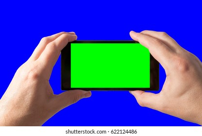 Man holds in two hands smartphone in landscape mode with green screen isolated on blue. Chroma key for placement of your own content.