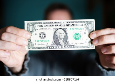 A man holds a U.S. 1 one dollar.