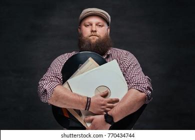 A man holds vinyl records.