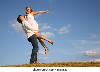 man holds woman in hands on meadow