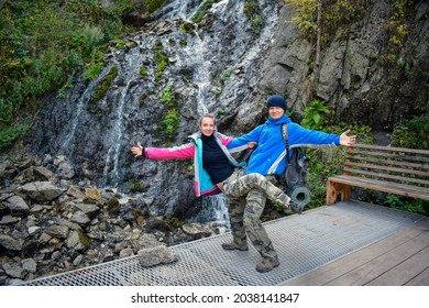 Man holds woman on his hands in strange pose near the Girl's Tears waterfall. Two funny and carefree hikers, male and female, having fun while showing a gymnastic exercise. Happy couple in mountains.
