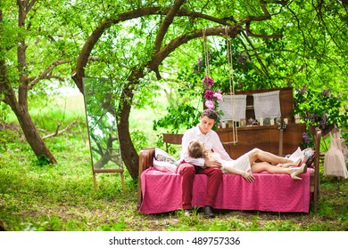 Man holds woman on his knees while resting on the pink bed in garden
