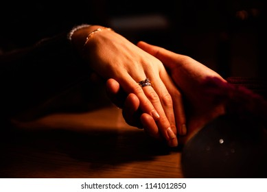 a man holds a woman's hand with an engagement ring and a gold bracelet