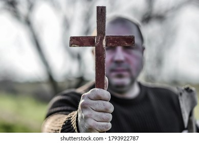A man holds a wooden Christian cross in front of him, an ax in his other hand. The concept of casting out demons on Halloween.
