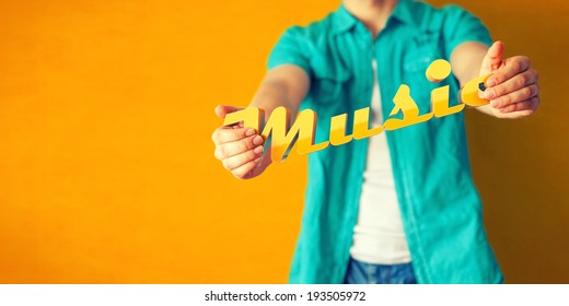 Man holds word Music on bright colorful background