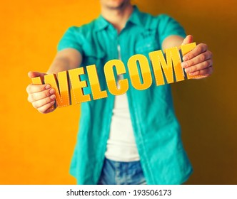 Man holds word welcome on bright colorful background