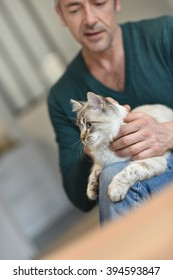 Man at home cuddling beautiful cat