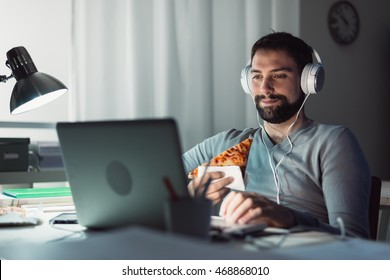 Man at home eating a slice of pizza and social networking with a laptop late at night
