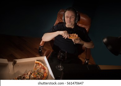 Man at home eating a slice of pizza and social networking with a lpc computer  late at night. Unhealthy Lifestyle.