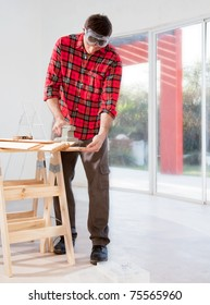 A man in a home interior sanding wood with an electric hand sander