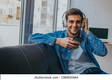 man at home with mobile phone and earphones