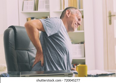 Man in home office suffering from low back pain sitting at the desk with notebook, papers and other objects