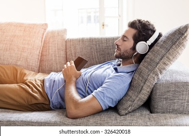 Man at home on sofa listening a music with a smartphone