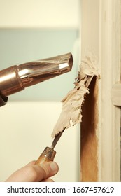 Man at home removing havy layer of old paint from door