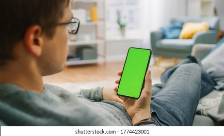Man at Home Resting on a Couch using Smartphone with Green Mock-up Screen. Guy Using Mobile Phone, Internet Social Networks Browsing.