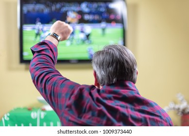 Man at home sitting on couch cheering at football game on TV screen