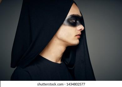 a man in a hood in a black mask on his face in a masquerade profile
