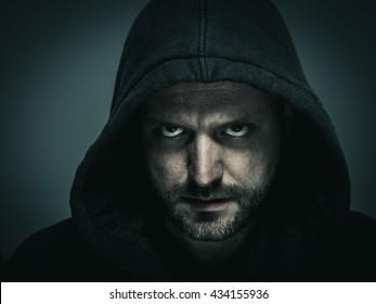 Man in hood. Man with facial hair. Dramatic portrait