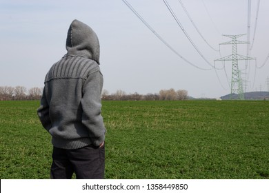 Man in hood as farmer is standing on green field looking around with an electric high voltage pylon with cables in background