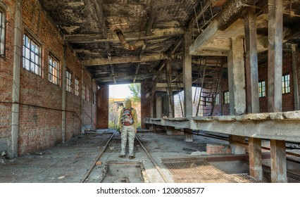 Man in hood and military clothes with backpack standing back to camera in old ruinde bricks abandoned building. Adventures seeker. HDR panoramic image