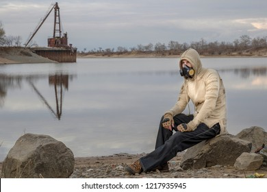 Man in hood, military gloves and respirator gas mask sits on stone near the river, with some abandoned industrial buildings on background. Maybe radioactive or chemical polluted zone. HDR image