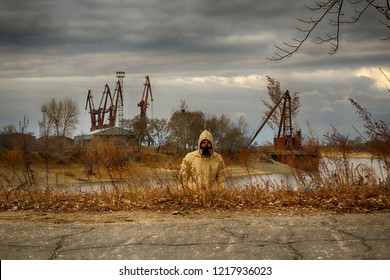 Man in hood, military gloves and respirator gas mask stay in high grass with some abandoned industriar ruins on background. Maybe biohazard, radioactive or chemical pollution zone. HDR image