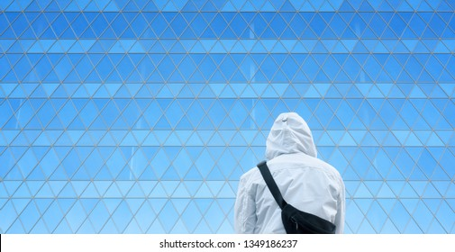 Man in a hood on the background of a modern building