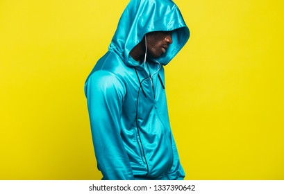 Man in a hooded shirt against yellow background. African man in a hoodie.