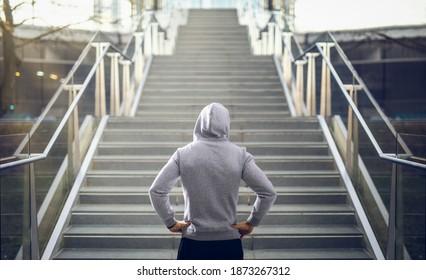 Man in hoodie preparing for stair run.