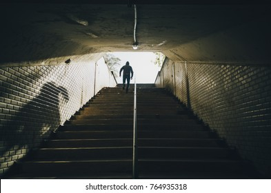 A man with hoody running up the stairs of an old tunnel in the city.