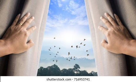 Man and hope concept . man opening window curtains and seeing the beautiful sky over the mountain