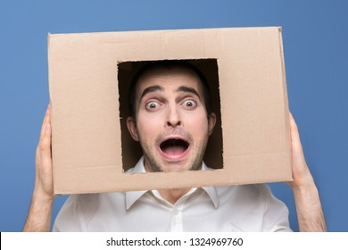 Man in horror, box on head, open mouth, looking at the camera, front view, blue background